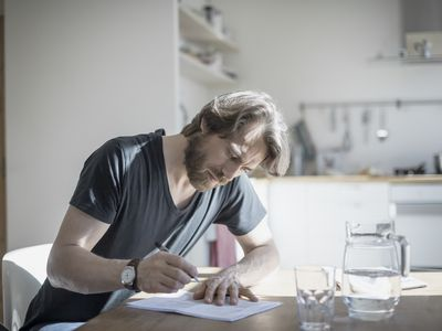 Man filling out tax forms at the dining room table