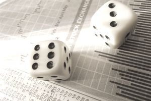 A pair of dice on a newspaper stock quote page indicating the risks associated with the timing of selling ESPP shares