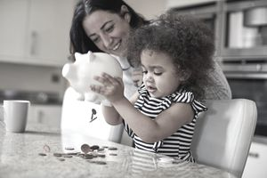Parent and child getting money from a piggy bank