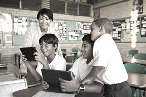 California teacher working with students using tablets in a classroom setting