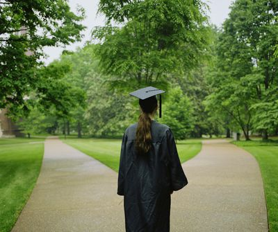 Female college student in graduation cap and gown, rear view