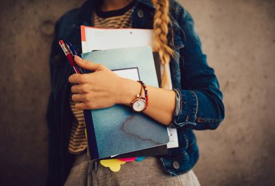 A young college student clutches textbooks, pens, and binders of papers