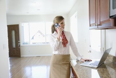 Female realtor using laptop and talking on cell phone in an empty house