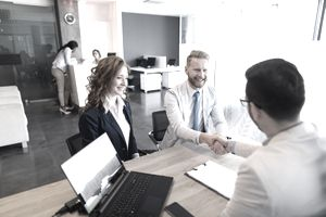 Couple talking to loan officer and shaking hands - stock photo