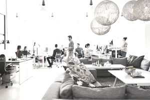 Office laborers sit at desks or mill about in an open concept working space.