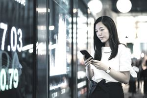 Confidence young Asian businesswoman checking financial trading data on smartphone by the stock exchange market display screen board in downtown financial district