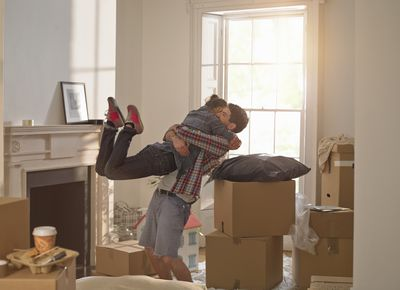 couple excited at being in their first home together hugging surrounded by boxes around