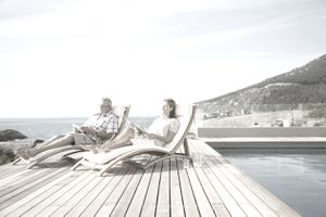Couple relaxing by pool.