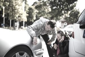 A man and woman examining a fender after a car accident.