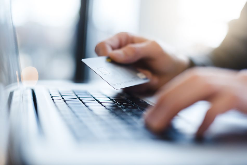 Man using laptop and holding credit card, close-up