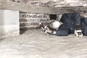 Man on His Back in Blue Coveralls, Mask and Helmet Holding Flashlight and Inspecting a Crawl Space Under a House