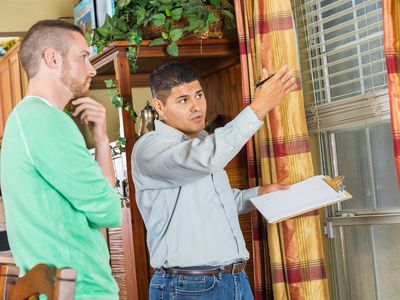 An inspector with a clipboard talks to a homeowner.