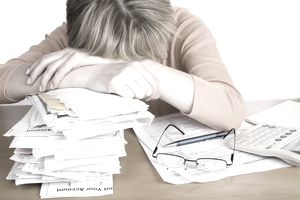 A woman with her head on a stack of bills overwhelmed by debt