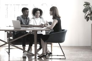 Young couple sits at table talking with female real estate agent about buying a house