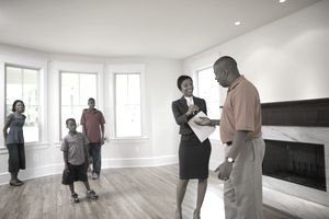 Realtor with family in the empty living room of a new home