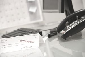 "A check marked ""direct deposit"" on desk next to a keyboard and a telephone"