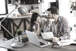 Couple sitting at kitchen table reviewing credit report