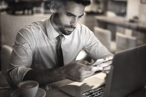 man on laptop and smartphone trading