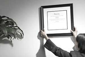 a woman hanging credentials on a wall