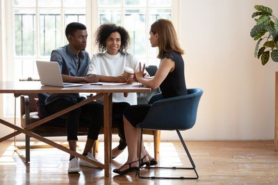 Young couple sits at desk talking with female real estate agent about buying a house