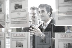 A couple looks at real estate postings in a window
