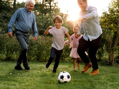 A multigenerational family plays soccer together in their backyard