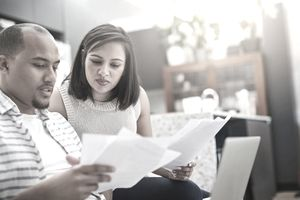 Young couple reviewing paperwork and looking troubled