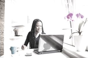 A woman with dreadlocks sits at a kitchen table, doing her income tax on a laptop