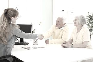 Senior couple shaking hands with consultant after discussing their retirement accounts