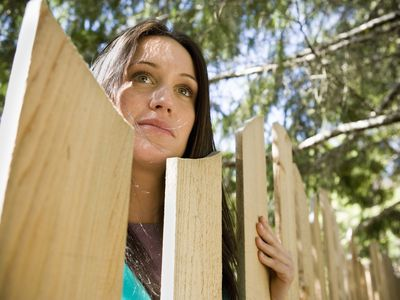 A person looks over a neighbor's fence