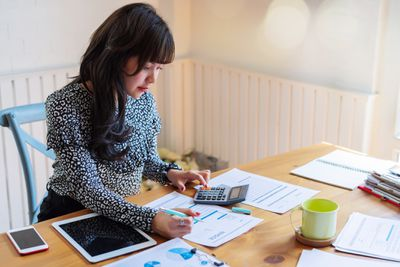 Businesswoman working at desk with paperwork, tablet, and calculator