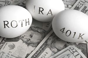 "Roth, IRA, and 401K ""nest eggs"" laying on a bed of twenty dollar bills for retirement"