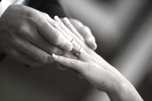 Closeup of bridegroom's and bride's hands putting on rings