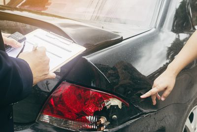 Cropped Hand Of Woman Showing Damaged Car to Insurance Agent