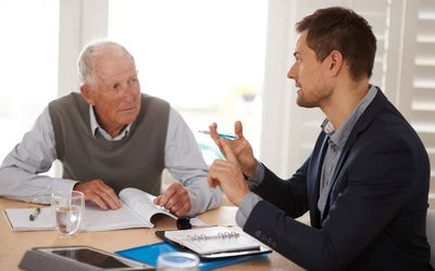 A male tax professional and an older man meeting at a kitchen table over paperwork