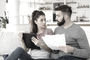 Couple going over their finances together at home using digital tablet