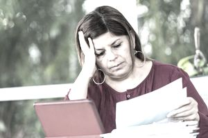 Frowning woman resting her head on her hand, looking at bills and a laptop