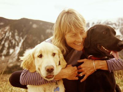 Mature woman hugs her two dogs in the mountains