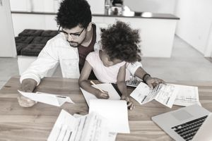 dad and daughter sitting at the counter doing bills