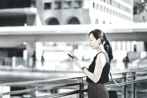 Businesswoman using smartphone on city bridge outside the business building in central business district.