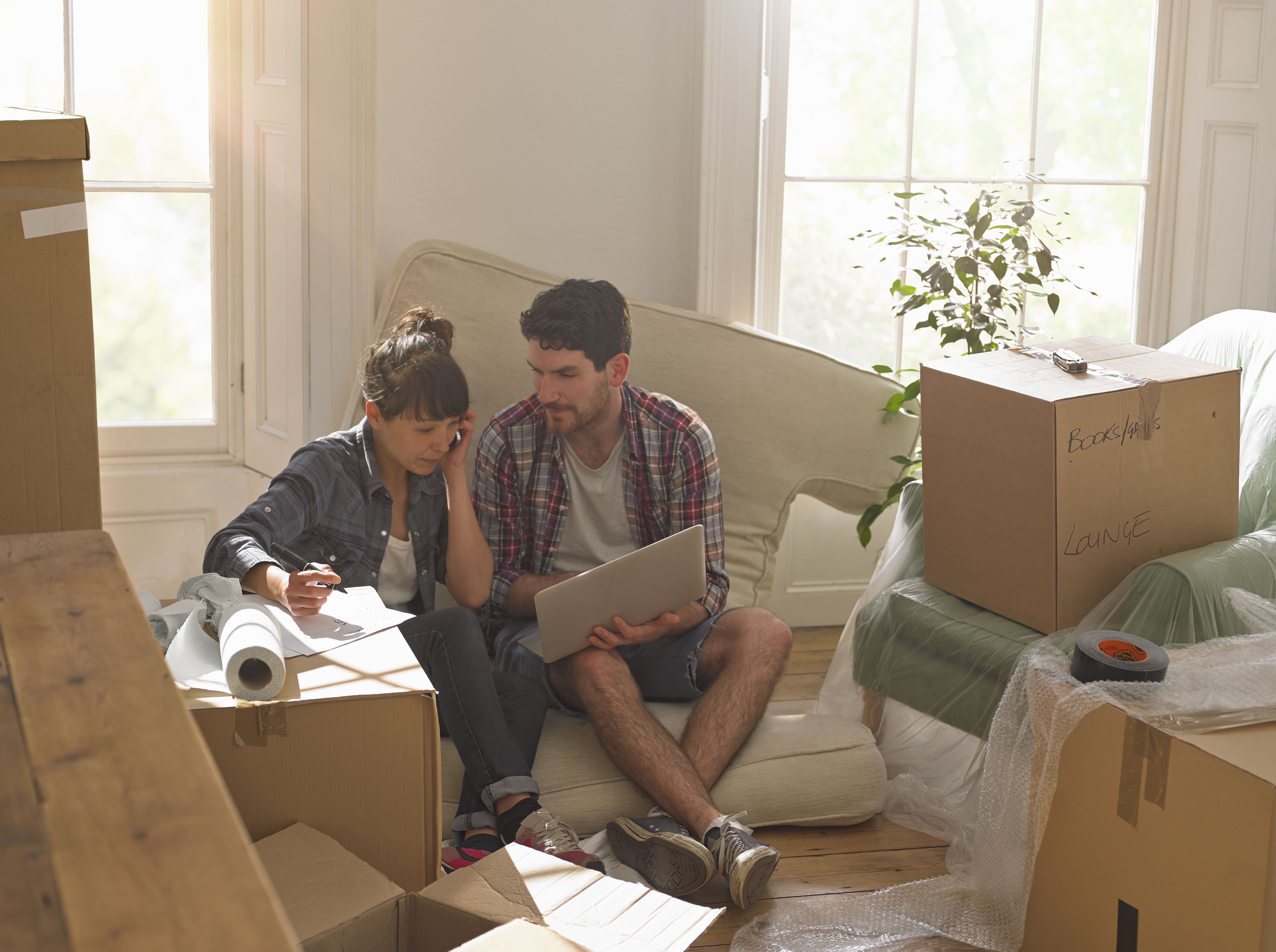 Couple moving into new home working on a laptop