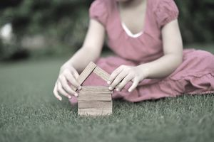 a young person building a home with building blocks