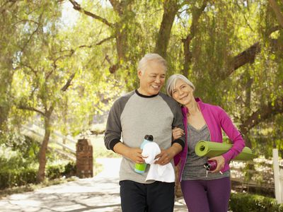 Mature couple with yoga exercise equipment walking in park