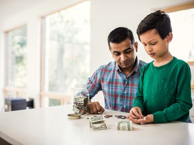 Father and young son count U.S. bills and coins at home