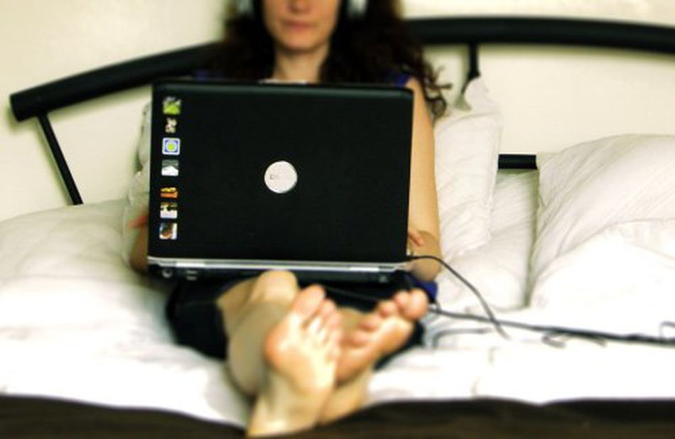 Person relaxing with laptop in bed. Paying bills online instead of licking envelopes.