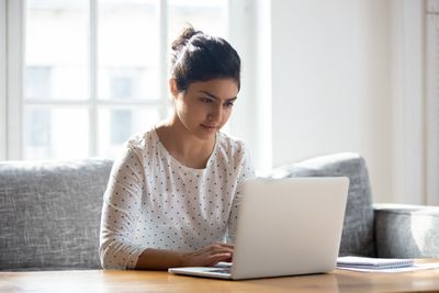 person in polka-dot white shirt looking intently at laptop screen