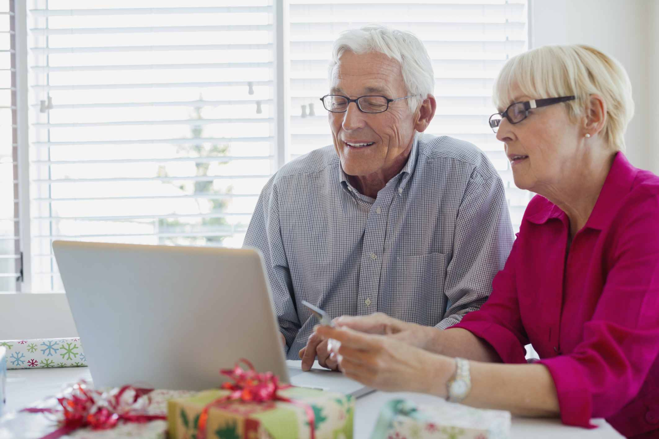Senior couple researching financial planners online.