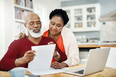 Couple reviewing financial documents at computer