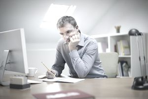 Upset man writing at desk in front of a computer