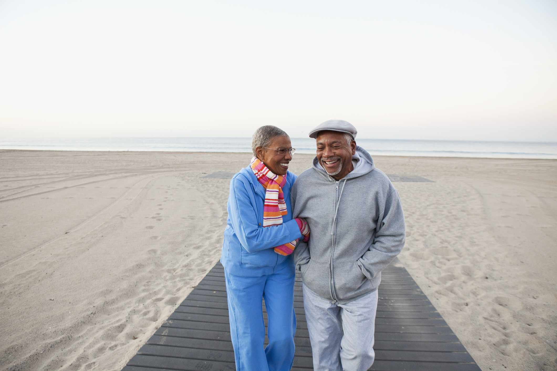A retired couple walking at the beach